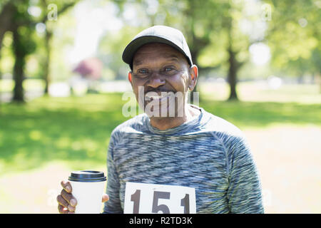 Portrait smiling, confident active senior man drinking coffee before sports race in park - Stock Image