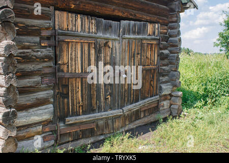 brown wooden door of old rustic barn in the siberian village on sunny summer day - Stock Image