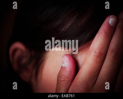 Girl hides face in hands - Stock Image