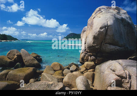 BEACH WITH LARGE ROCK AND ISLAND VIEW, SEYCHELLES, ISLAND, EAST AFRICA. JUNE 2009. The beautiful islands of the Seychelles in the Indian Ocean offer p - Stock Image