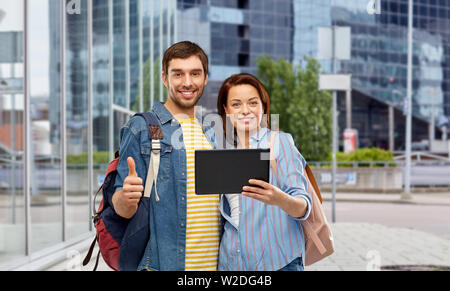 couple of tourists with tablet computer in city - Stock Image