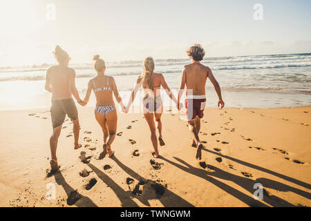 Group of young people friends enjoying with fun the summer holiday vacation running at the beach to the water in playful outdoor leisure activity toge - Stock Image