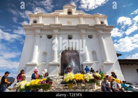 Local Guatemalan People Burning Incense and Selling Yellow Flowers in Front of Iglesia De Santo Tomas on a Market Day in Chichicastenango Village - Stock Image