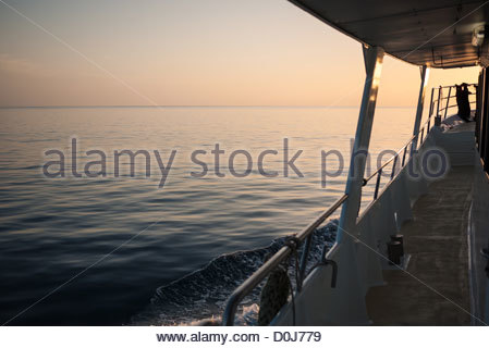 Very calm seas at sunset on the Great Barrier Reef. At right of frame is part of the MV Night Crossing, a charter - Stock Image