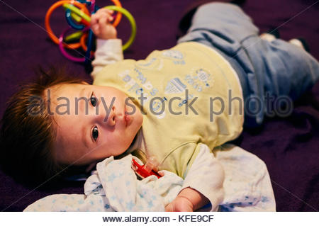 Baby boy lying on a blanket with a toy in his hand - Stock Image
