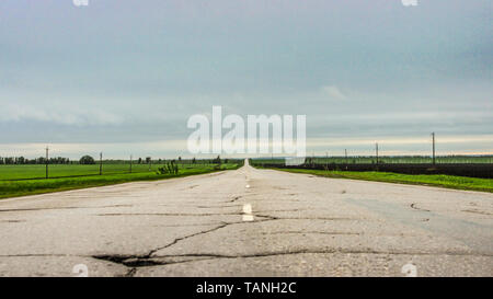 Landscape with a view of the old empty asphalt road through the fields - Stock Image