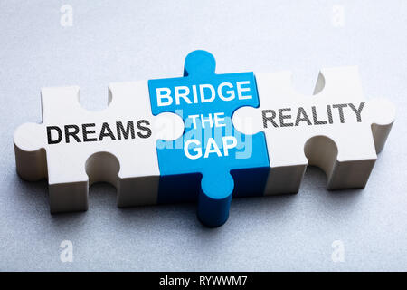 High Angle View Of Text On Puzzle Piece Over Gray Backdrop - Stock Image