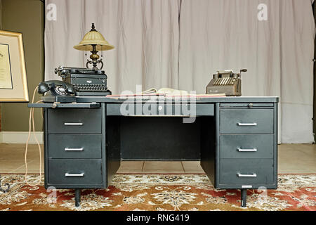 Old vintage antique steal or metal desk with a black telephone, manual typewriter and hand crank calculator circa 1940s or 1950s on display. - Stock Image