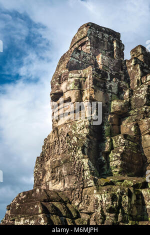 One of the 216 giant faces that adorn the great Bayon Temple in Angkor Thom in Cambodia. - Stock Image