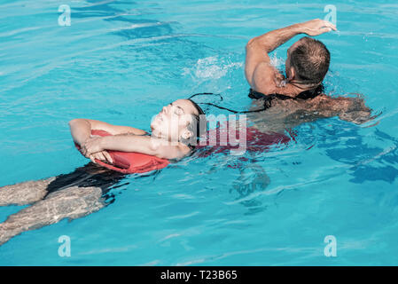 Lifeguard in training, rescuing woman from water. - Stock Image