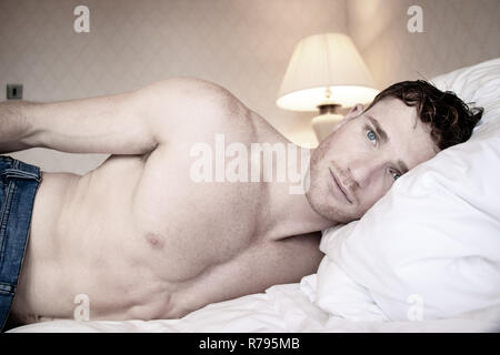 Good looking shirtless hunk wearing blue jeans like on hotel room bed sheets - Stock Image
