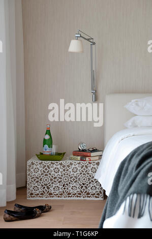 Table and shoes by bed in modern bedroom - Stock Image