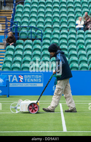 Groundsman paints the white lines on a grass tennis court with a machine as spectators watch on from the stands - Stock Image