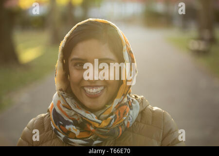 Portrait smiling, confident Muslim woman wearing hijab in park - Stock Image