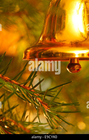 A golden  bell is hanging on the Christmas tree. - Stock Image