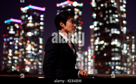 Side view of businessman against night view of city - Stock Image