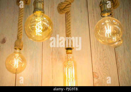 Rope light bulbs over weathered wooden background. Low angle view - Stock Image