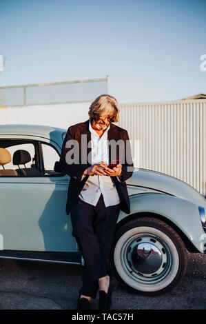 Senior man standing in front of vintage car using mobile phone - Stock Image