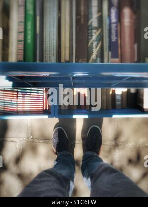 Standing in a secondhand bookstore searching for rare books. Cambridge United Kingdom - Stock Image