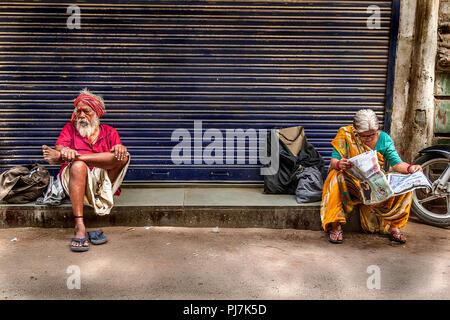 Senior citizen woman reading newspaper and senior citizen man sitting nearby - Stock Image