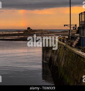 Looking out to an old stone shelter and the sea from Seahouses harbour with a dramatic sky at sunset - Stock Image