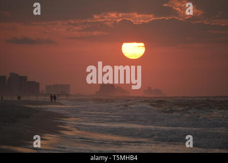Bright sunrise, with clouds, along beach over Atlantic Ocean with waves breaking along shoreline, in Gulf Shores, Orange Beach, Alabama, USA - Stock Image