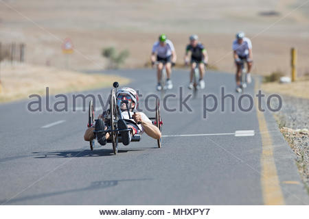 Disabled racing cyclist riding recumbent bicycle on open road - Stock Image