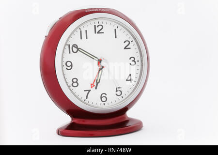 Red analogue alarm clock with luminous hands showing time at ten minutes to seven just before the alarm goes off in the morning. - Stock Image