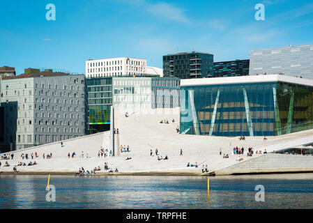 Opera House Oslo, view across the fjord of people on the vast access ramp leading to the roof of the Oslo Opera House, with Barcode Buildings beyond. - Stock Image