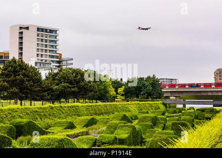 Plane landing over the Thames Barrier Park, London Docklands, UK - Stock Image