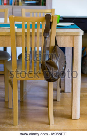 Brown leather women bag hanging on a wooden chair - Stock Image