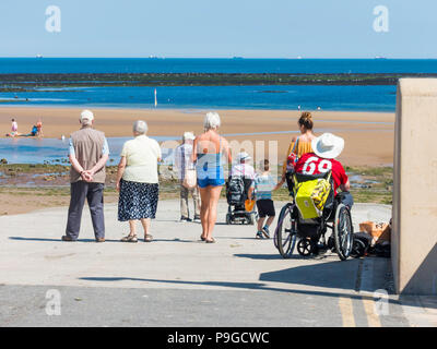 Sunny summer Sunday people walking down a ramp to enjoy Redcar beach - Stock Image
