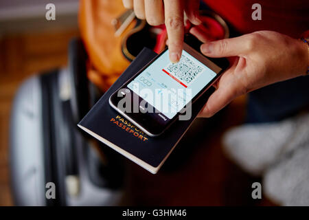 Woman holding passport and smartphone, smartphone showing QR code, overhead view - Stock Image