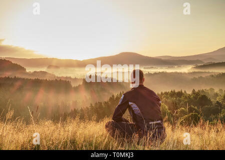 Man sitting on hill summit. Conceptual scene. He was wearing light outdoor clothes. He was looking forward with determination - Stock Image