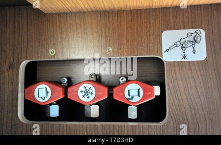 Knobs inside a camper to open and close the heating,refrigerator and gas for cooking - Stock Image