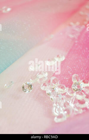 A beautiful and elegant macro of glitter from sparkling diamonds with bokeh or depth of field and pink texture as background - Stock Image