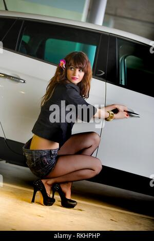 Beautiful and attractive young woman acting car thief cautious looking back over shoulder  young woman legs heels - Stock Image
