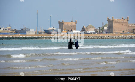 two young Islamic girls wearing Hijab enjoying the sea at Essaouira beach - Stock Image