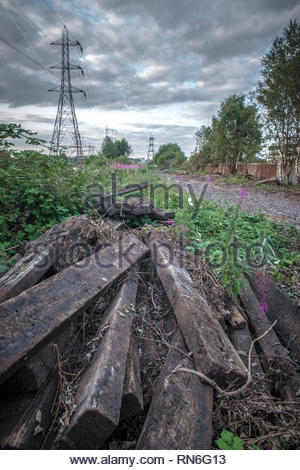 Dismantled sleepers lying next to former railway tracks, Ocker Hill, West Midlands - Stock Image