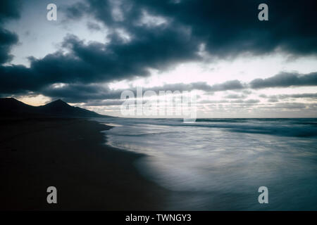 Cold tones sea and shore after the sunset durint the evening dawn before the night - nobody people there and long exposure technic - blue colors for s - Stock Image