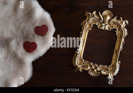 antiq golden photo frame in Rococo style, on dark rustic wooden background with white Tuscan sheepskin and hearts - Stock Image