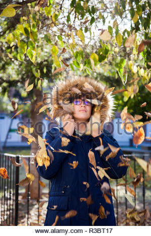 Beautiful teen poses with her coat among the autumn leaves in a sunny afternoon - Stock Image