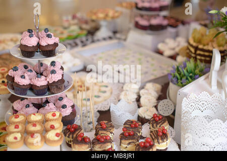 Delicious cupcakes with berries on a tiered cake-stand and a large assortment of sweets and cakes at a candy buffet catered for a formal event - Stock Image