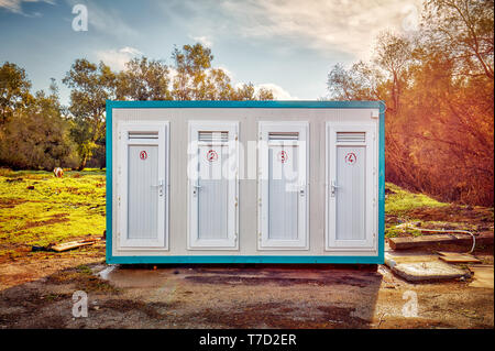 Prefabricated portable cabin with four numbered doors on a meadow field in the forest - Stock Image