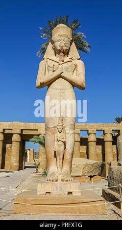 A statue of Rameses II with the smaller statue of his daughter Bent'anta  at the Karnak Complex, or Temple of Karnak, Luxor, Egypt - Stock Image