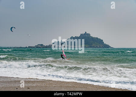 Marazion, Cornwall, UK. 13th April 2019. UK Weather.  Windsurfer and Kitesurfers were out in force on the sea at Marazion, making the most of the very windy conditions. Credit: Simon Maycock/Alamy Live News - Stock Image