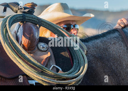 USA, California, Parkfield, V6 Ranch portrait of out of focus cowgirl with her horse, lasso in the foreground (MR) - Stock Image