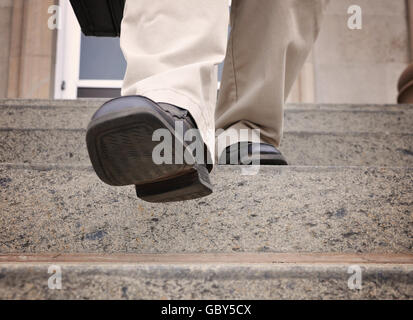 A business man is stepping down the stairs at an office for a power, challenge or motivation concept. - Stock Image