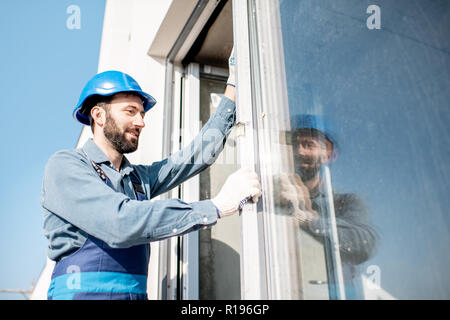 Workman in uniform mounting windows checking the level on the white building facade - Stock Image