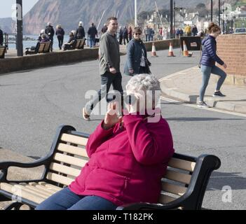Sidmouth, UK. 24th Mar, 2019. Visitors take a good look around the seafront on a sunny day in Sidmouth. Credit: Photo Central/Alamy Live News - Stock Image